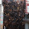 1550 Chairs Stacked Between Two City Buildings